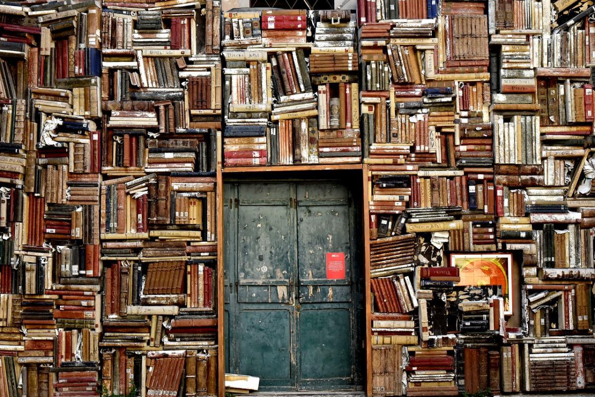 Paljon vanhoja kirjoja isossa hyllyssä