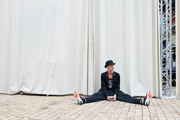 Esiintyjä istuu hattu päässä lattialla
