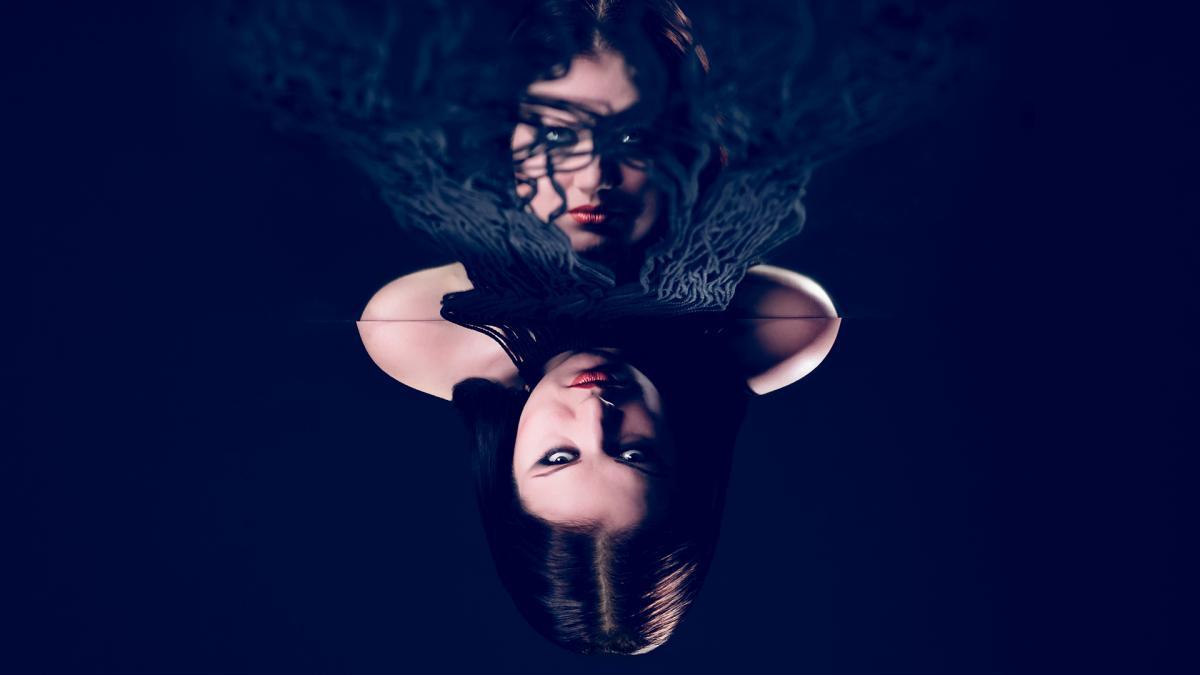 Nainen ja peilikuva tummaa taustaa vasten