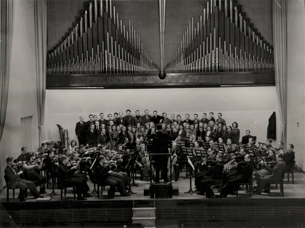 The organ pipes built in 1939 dominated the background of the stage in the concert hall until their dismantling in the early 1990s. The student orchestra and choir in an undated image.
