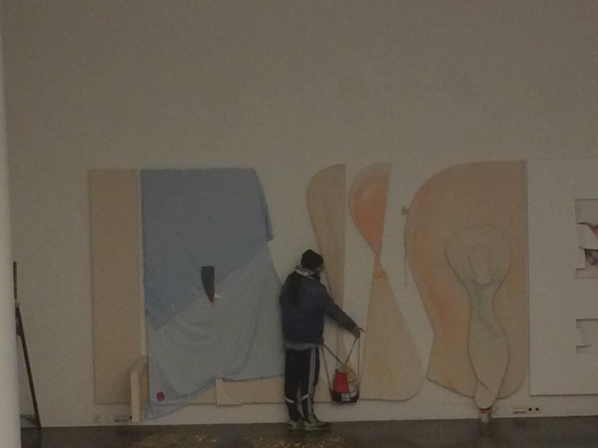 Hämärä kuva galleriatilassa olevasta koko seinän kokoisesta taideteoksesta, joka näyttää koostuvan pastellinvärisistä kirjaimia muistuttavista abstrakteista rakennelmista. Teoksen edessä seisoo tummiin pukeutunut ihminen selkä kameraan päin.