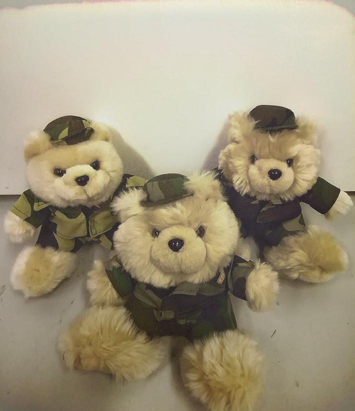 Kolme vaaleaa pehmokarhua maastokuvioisissa armeijatakeissa ja -hatuissa