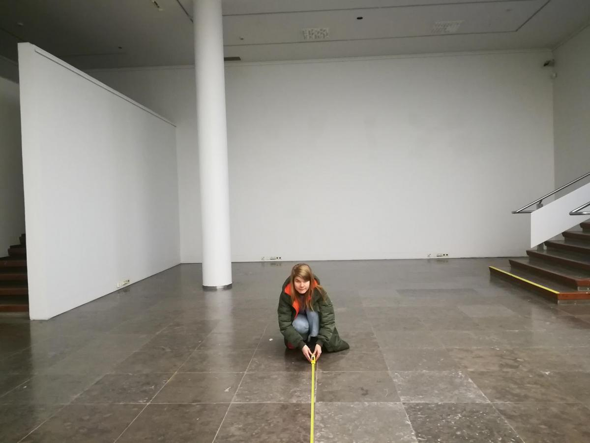 Tyhjä valkoinen huone, jonka keskellä nuori nainen ulkovaatteissa on kyykyssä lattialla mittanauhan kanssa. Keltainen mittanauha on auki monen metrin verran kohti kameraa.
