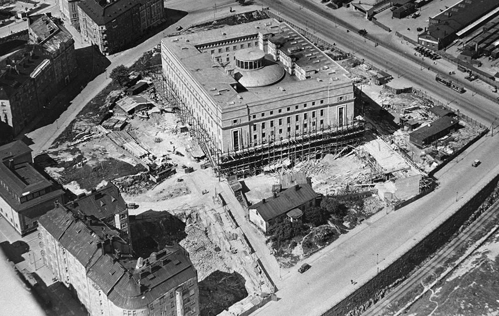 Flygbild av byggandet av riksdagshuset och dess miljö 1930. Nere på bilden syns konservatoriebyggnadens tomma tomt där berget sprängts.