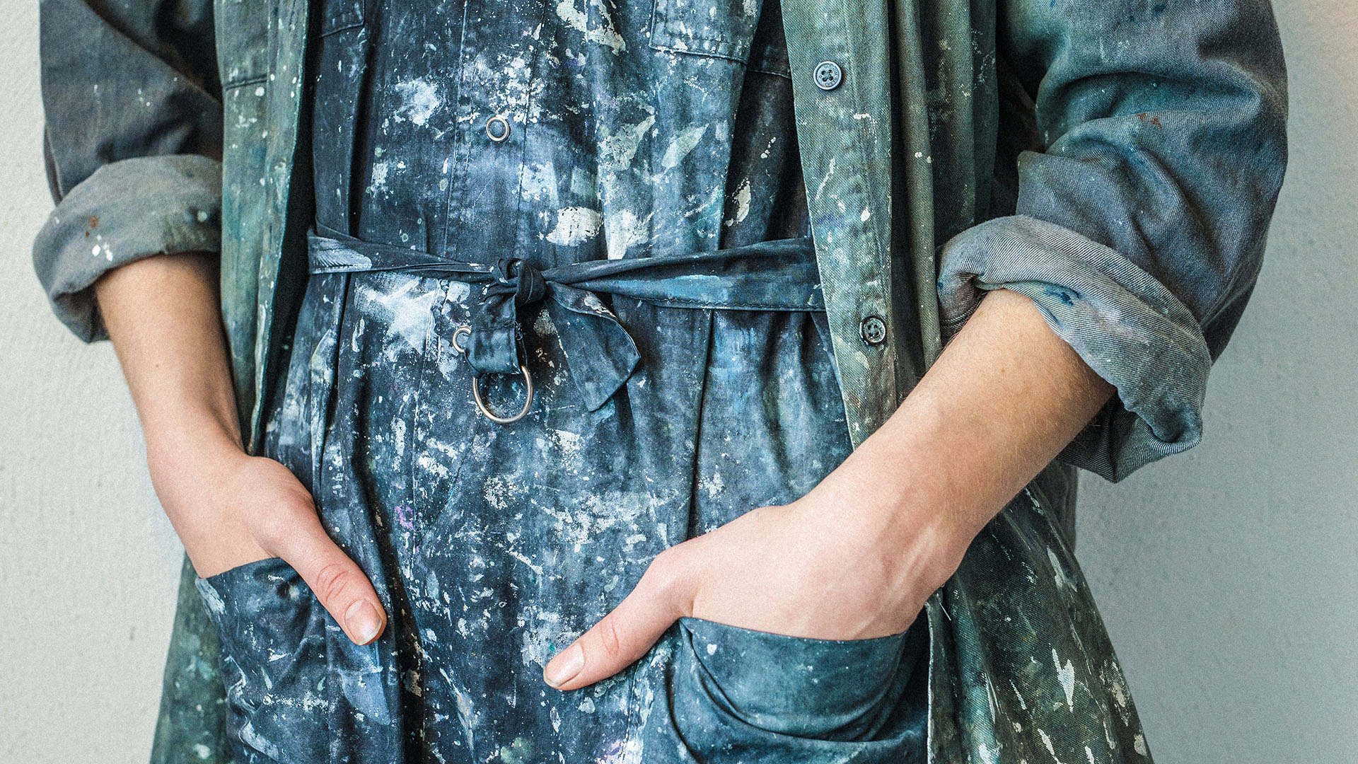 Close up of hands in the pockets of an apron splattered with paint.