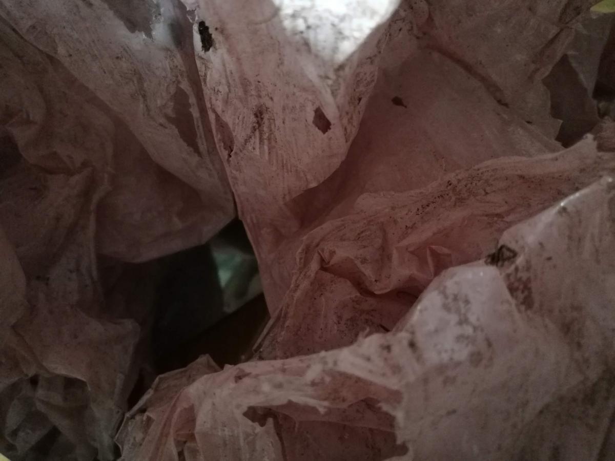 Roikkuvaa, paikoin likaista ja revennyttä muovikangasta, jossa hienoinen vaaleanpunainen ja valkoinen sävy.