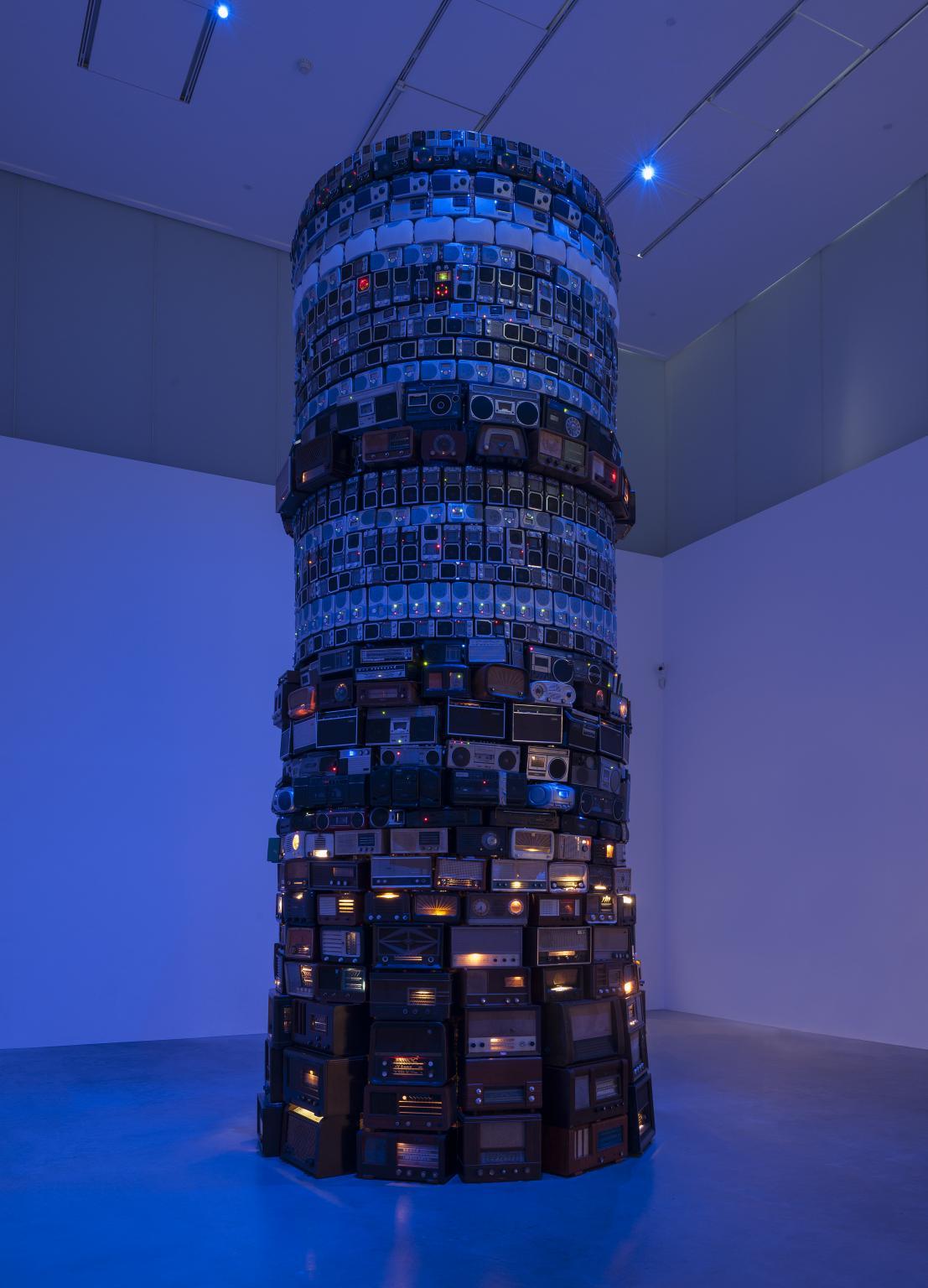 Soikea, korkea torni, joka on päällystetty sadoilla erilaisilla radioilla ja stereoilla. Jokainen rivi on erilainen, mutta sisältää keskenään mahdollisimman samanlaisia radioita. Kuvassa on sinertävä valotus ja osassa radioista on päällä pieni valo.