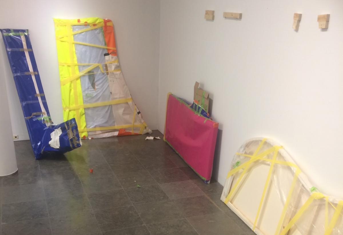 Valkoseinäoisen huoneen nurkka. Seiniä vasten nojaa paketteihin käärittyjä parin metrin kokoisia erimuotoisia levyjä. Levyt on kääritty esimerkiksi sinisiin, pinkkeihin, valkoisiin ja keltaisiin kääreisiin.