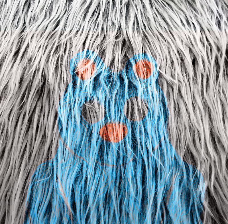 Lähikuva harmaasta turkista, jossa osa karvoisa on värjätty sinisellä ja punaisella. Värit muodostavat karvaan sinisen nallekarhun, jjolla on punaiset pallot korvina ja nenänä.
