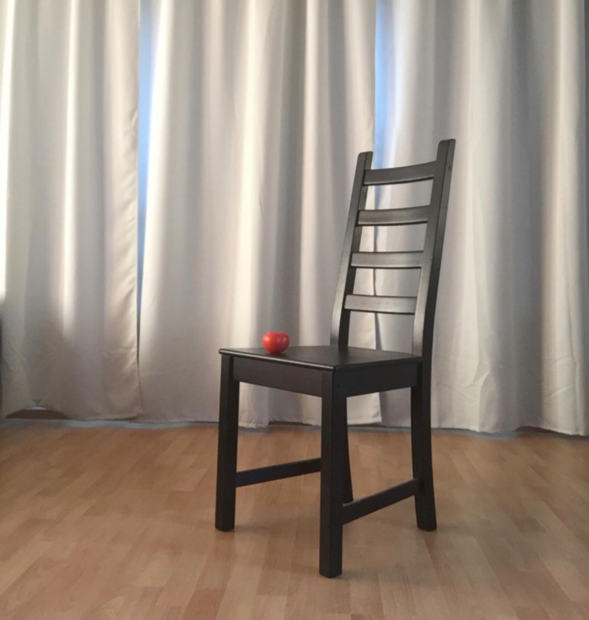 Tuoli harmaan verhon edessä, tuolilla tomaatti