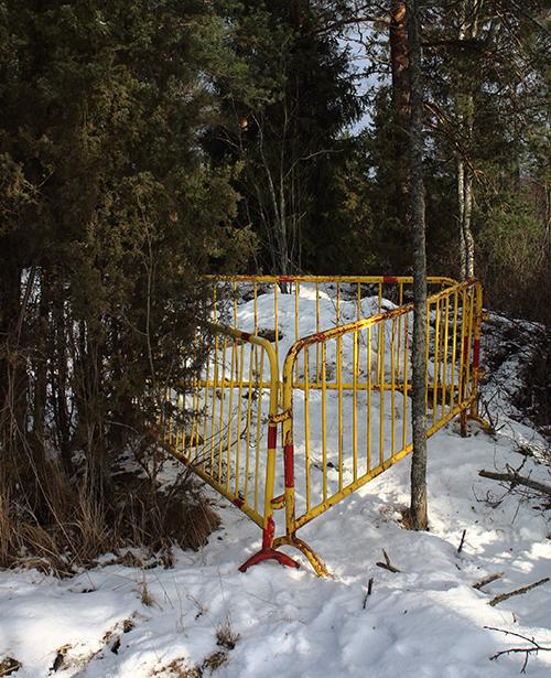 Havumetsä talvella, maassa on lunta. Puiden lomaan on asetettu kolme parin metrin mittaista tietöissä käytettävää kelta-punaista metalliaidan palaa kolmion muodostelmaan.