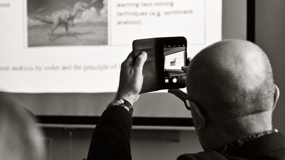 Mies ottaa kuvaa puhelimella screenistä