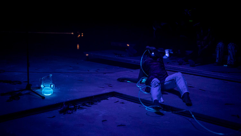 Henkilö lattialla pimeässä sinisävyisessä tilassa. Lattialla hohtava lasikannu, henkilöllä päässään erikoiset katselulasit.