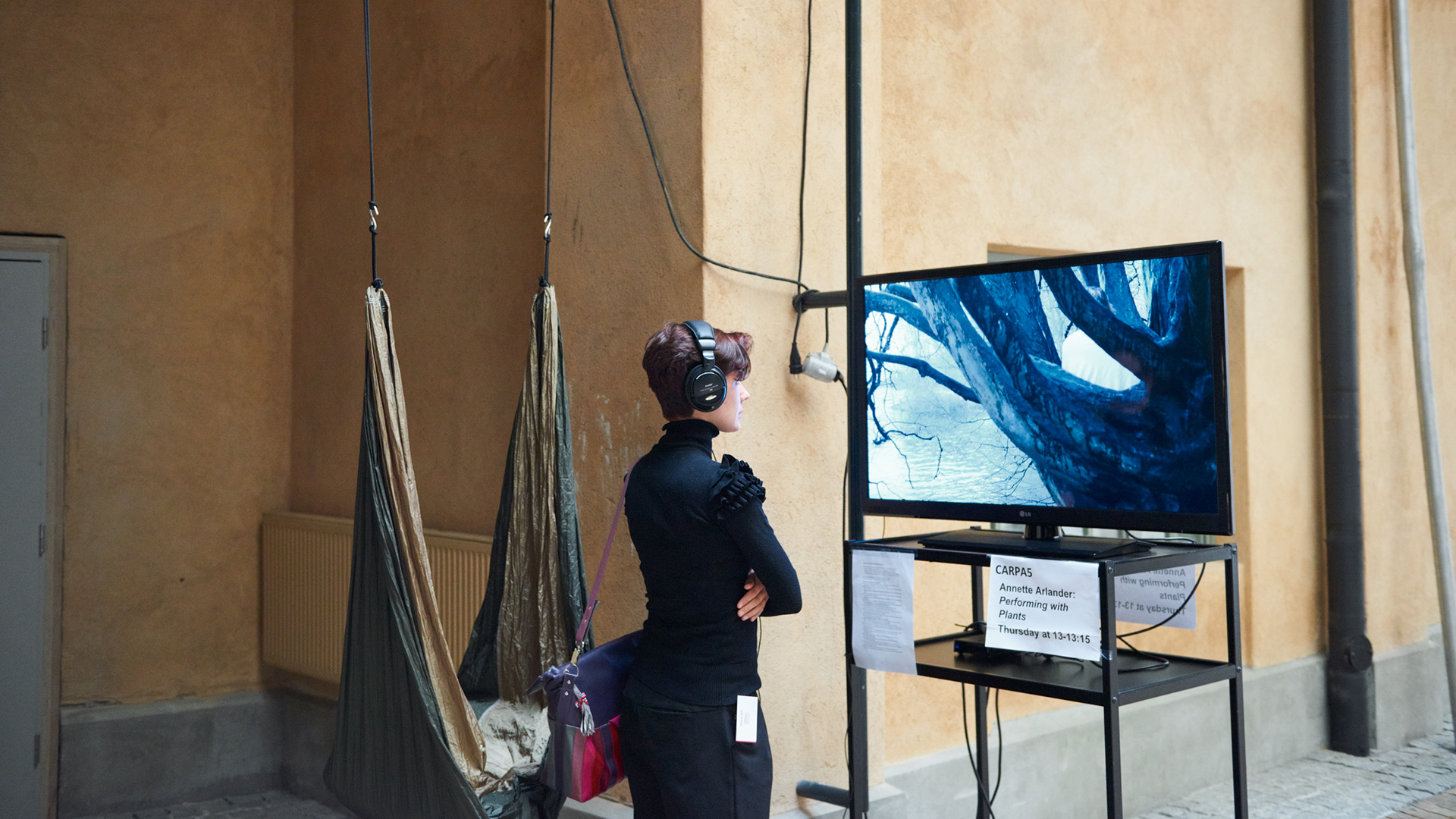 Person watching a video installation wearing a headset. Located in the Theatre Academy's premises.
