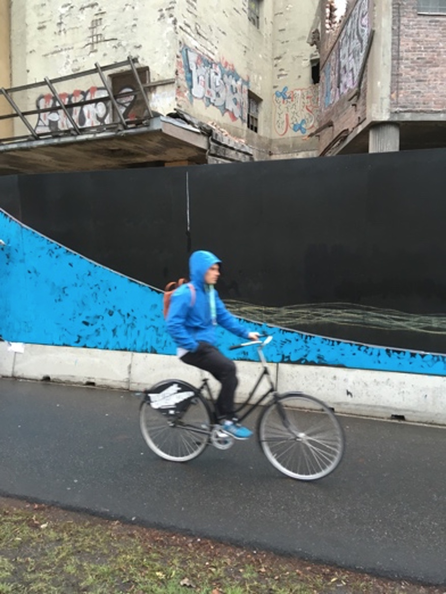 a person riding a bicycle in front of a balck and blue construction site fence