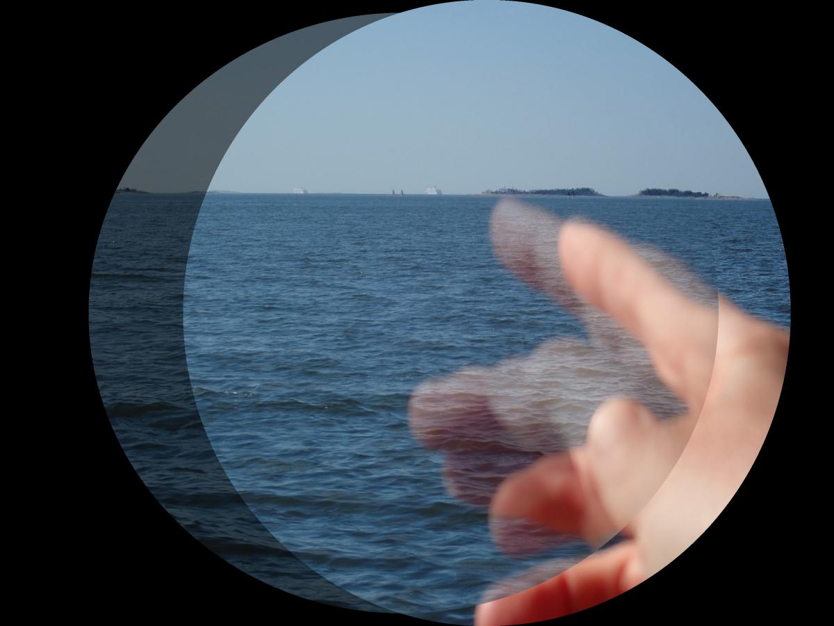 stereoscopic superimposition showing a hand reaching toward the horizon at the sea.