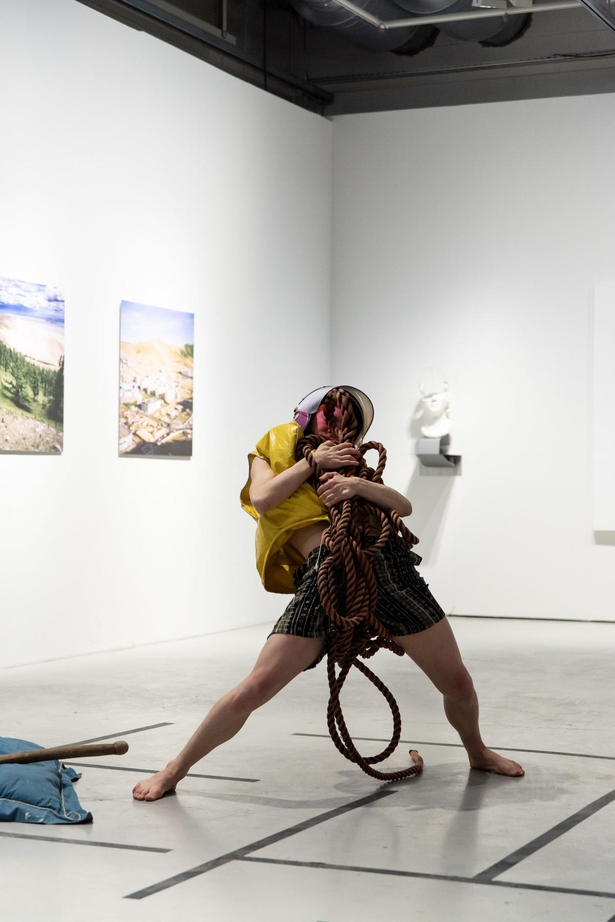 A person wearing a pink former police helmet and a yellow life jacket is holding a bundle of red sea rope close to their chest. The person has a wide stance and is leaning back in their posture. They are performing in a gallery with some artwork behind them.