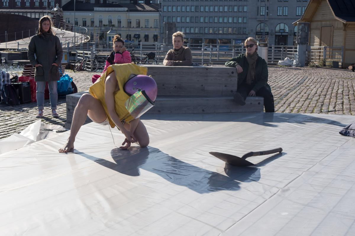 A person wearing a pink former police helmet and a yellow life jacket is squatting on the wooden stage outdoors in Kauppatori. There is a metal shovel next to the person. Several people are watching the performance.