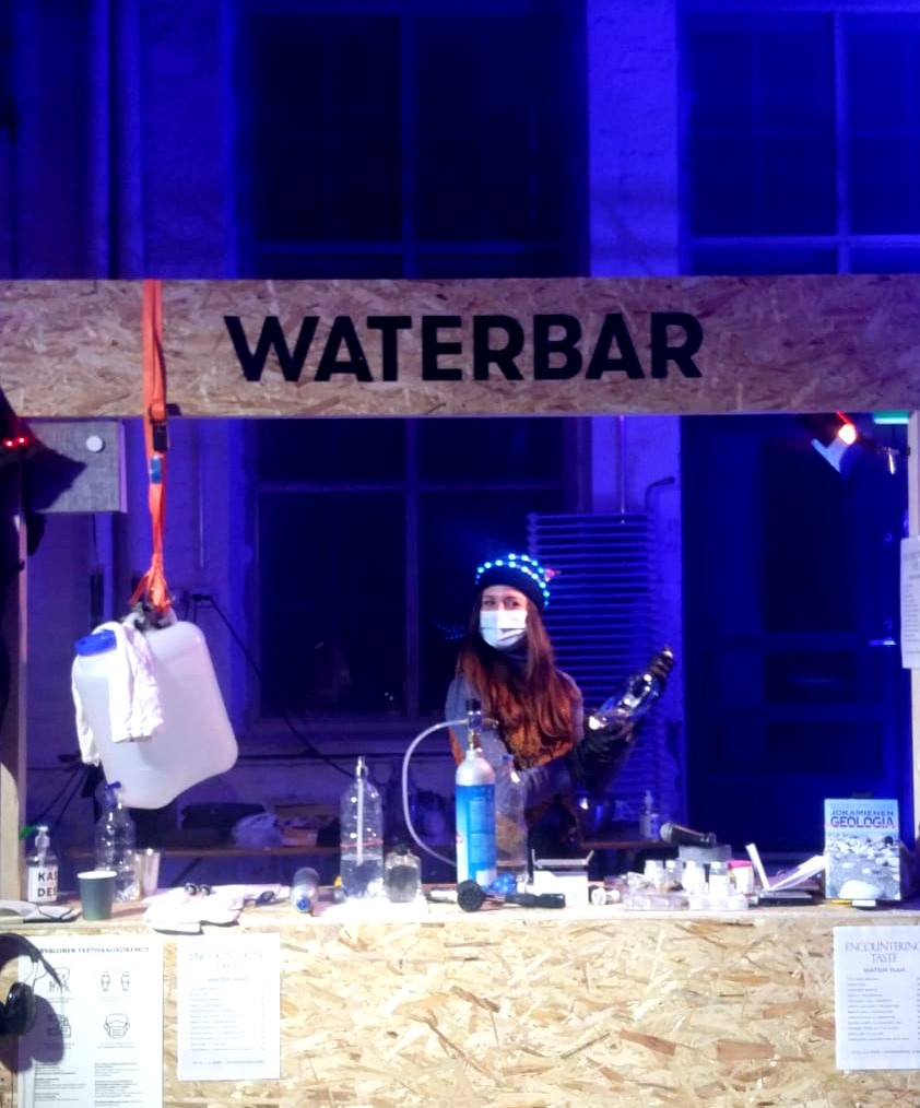 The picture shows the water bar set during ANTI festival Prize Party. At the water bar, you could taste waters from different areas of Finland and mineral waters synthesized using natural and artificial mineral samples. In the photo, artist Tea Andreoletti is behind the counter as she prepares sparkling water through a carbonization process.