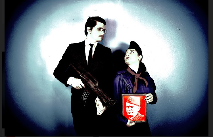 The Missing Torch video performance promo image with Fjolla Hoxha as the Adult Pioneer, wearing a pioneer uniform and holding a riso printed image of Tito, the leader of ex-Yugoslavia and Dylan Simon as the Travel Agent in a suit, holding a machine gun. They are looking at each other.