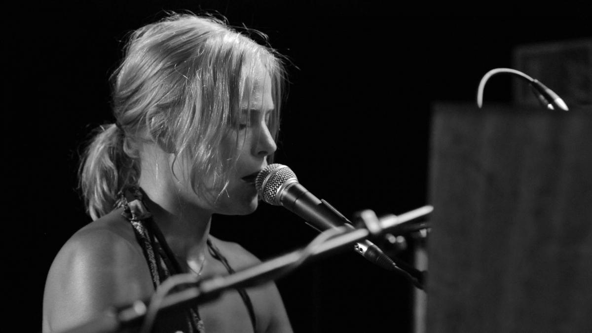 Susanna Lukkarinen soittaa pianoa ja laulaa mikrofoniin. Kuva on mustavalkoinen.