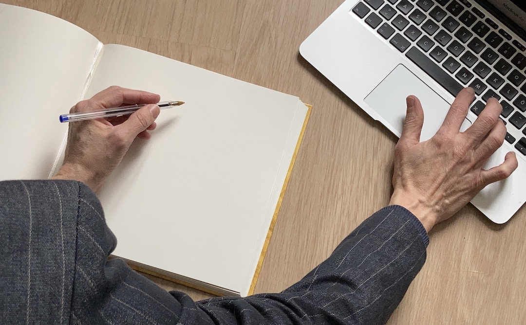 Left hand holding a pen on a notebook, right hand on the keyboard of a laptop.
