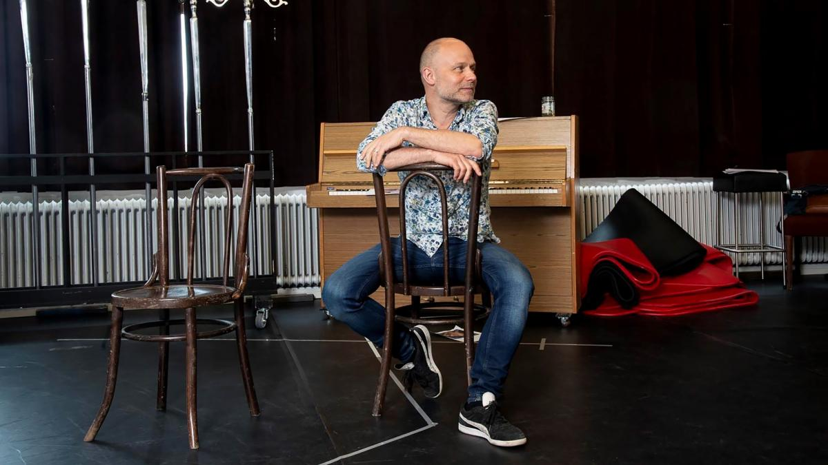 Jussi Tuurna istuu tuolilla teatterilavalla. Hän katsoo oikealle ja hymyilee. Hän istuu tuolissa väärinpäin, eli nojaa käsillään selkänojaan.