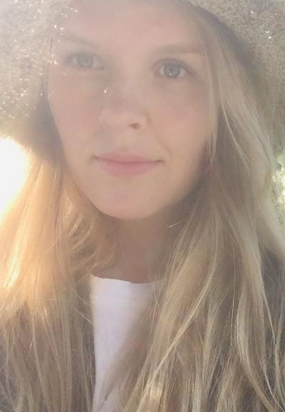 Tuuli Kainulainen hymyilee selfiessä kesäauringossa.